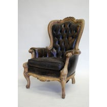 Ornate carved brown leather armchair