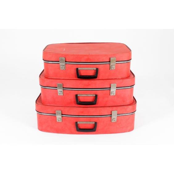Three vintage red vinyl suitcases image